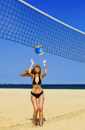 Attractive woman plays in beach volleyball photo