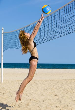 Attractive woman plays in beach volleyball Stock Photo - 5341185