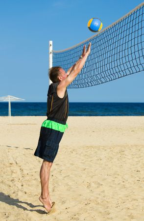 Sports man plays in beach volleyball photo
