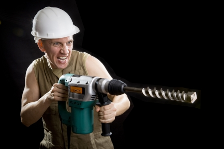 drill bit: The builder in a protective helmet holds the professional puncher-hammer with a drill of the big diameter