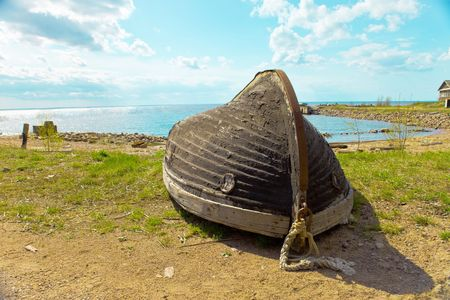 overturned overturn: The turned boat on seacoast a bright sunny day