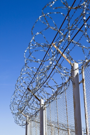 prison wall: Fence with a barbed wire