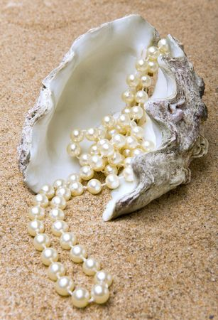 The shell with a pearl beads lies on sand