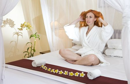 The young woman in house clothes on a bed Stock Photo - 5983235