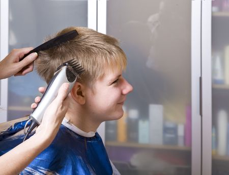 clippers comb: The happy teenager in hairdressers salon