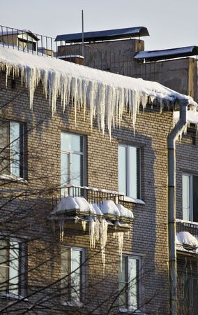 Huge icicles hang down from roof photo