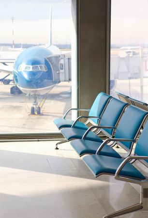 terminal: Empty armchairs in hall of expectation of airport and plane behind window   Editorial