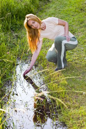 Young woman in Field at creek photo