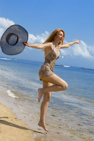 Young graceful woman goes on coast of ocean with straw hat in hands photo