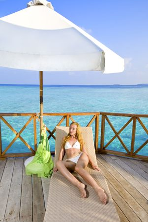 Young woman on chaise lounge under umbrella. 