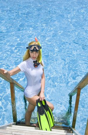 Sports woman stands with equipment for Snorkeling on steps of villa on piles on water.  Maldives.   photo