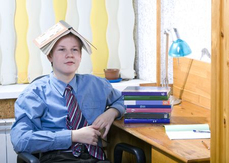 tiring: Pupil schoolboy reflected with pile of textbooks above performance of homework