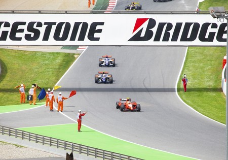 racecar: BARCELONA- MAY 9: The support personnel waves flags to finishing bolides of stage of race JP2 on may 9, 2010  in Barcelona, Spain
