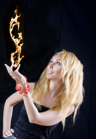 Beautiful blonde magician with fire, taking off from hand   photo