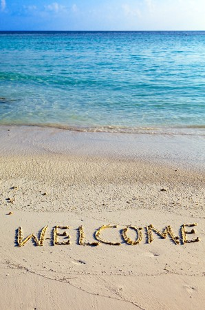 Word  welcome   is written on sand on oceanside photo