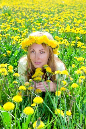 Young pretty woman in wreath of dandelions in the meadow solar day photo