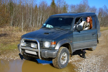Young woman behind rudder of offroad car on dirt road before water obstacle photo