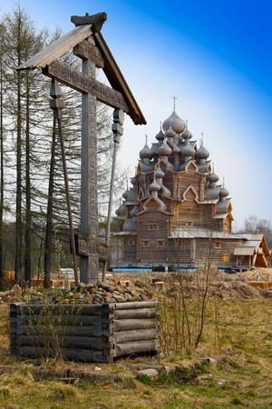 Cross before Wooden orthodox church in name of Cover All-holy mother of God, Russia (Pokrovskaya church)   photo