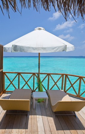 Parasol and chaise lounges on a terrace of water villa, Maldives. Stock Photo