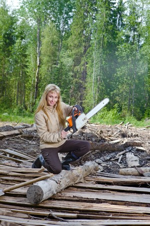 The young woman in wood saws a tree a chain saw photo