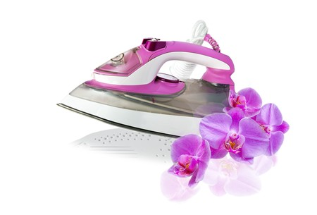 modern new pink  electric iron and orchid flowers on white background photo