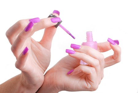 pink nails: The female hands doing manicure and a bottle of nail polish