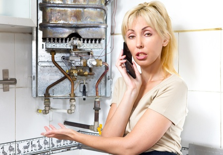 The young woman the housewife calls in a workshop on repair of gas water heaters Stock Photo - 8354086