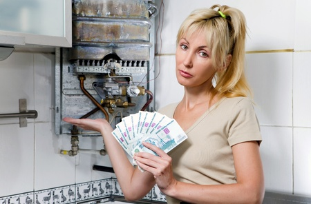 The sad woman the housewife counts up money for repair of a gas water heater   photo