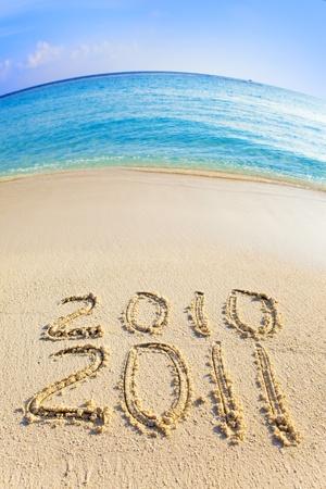 On sand at ocean edge it is written 2010-2011 photo