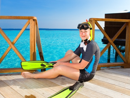 Boy-teenager with flippers, mask and tube at ocean. 