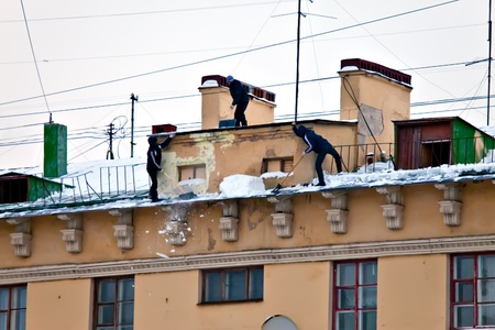 Russia. Petersburg. Workers clean snow and icicles from a house roof photo