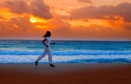 Silhouette of woman, running on sunset along ocean coast photo
