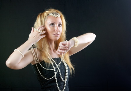 beautiful young blonde woman with long hair and a pearl beads on dark background.   photo