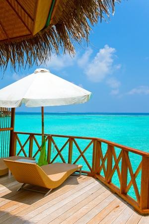 blue lagoon: Ombrellone e chaise lounges su una terrazza di villa di acqua, Maldive. Archivio Fotografico