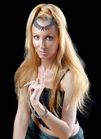 beautiful young blonde woman with long hair and jewellery, warning sign points a finger on dark background   photo