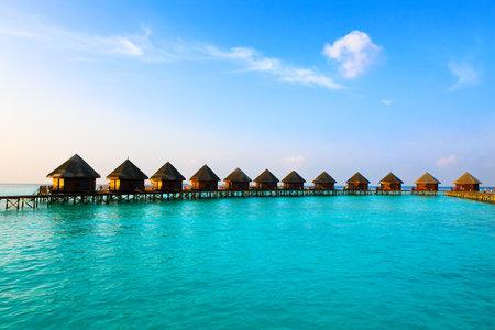 Maldives. Villa auf Pfähle auf dem Wasser Sonnenuntergangs Zeit. Standard-Bild - 9238825