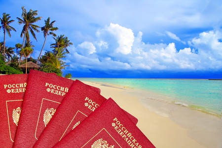vacation destinations: International passports of Russia against a tropical beach - the international passport your admission for holidays