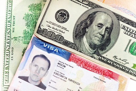 The American visa on page of the Russian international passport and US dollars photo