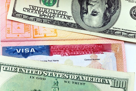The American visa on page of the international passport and US dollars photo