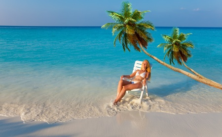 paradise bay: The girl in a chaise lounge at ocean under palm trees on a sunset Stock Photo