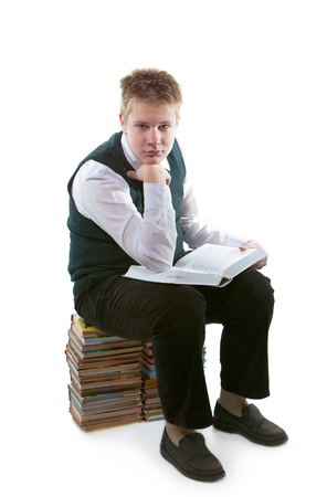 The schoolboy in a school uniform sits on a pack of books, with the opened book in hands photo