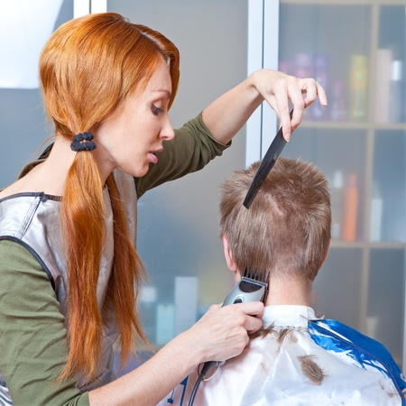 The beautiful young woman the hairdresser does a  hairstyle to the client - young man photo