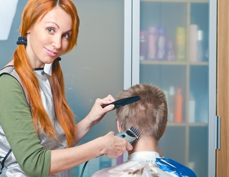 The beautiful young woman the hairdresser does a  hairstyle to the client - young man Stock Photo - 9333592