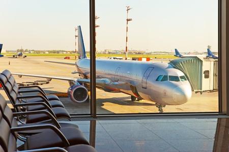 창 뒤에 공항의 기대와 평면 홀에서 빈 의자