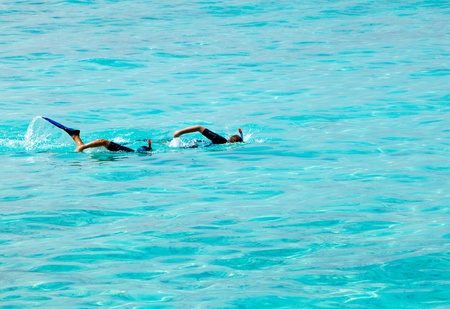 synchronously: Two men with masks and tubes swim synchronously at ocean Stock Photo