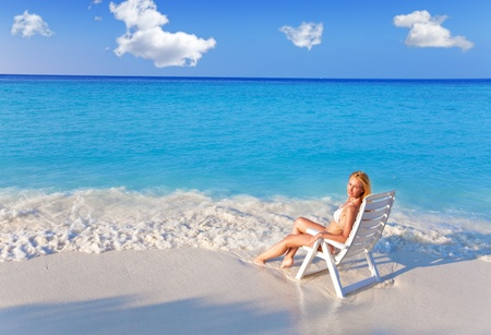 Young pretty woman tans in beach chair, it put in ocean Stock Photo - 9751099