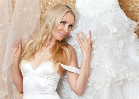 The happy bride tries on a wedding dress   Imagens