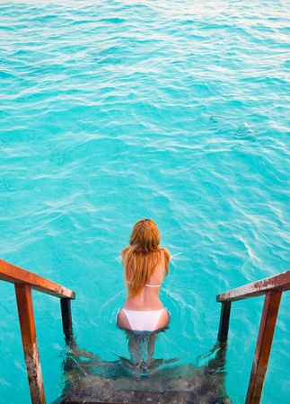 Maldives.  Young sports woman swims from steps of villa on water  photo