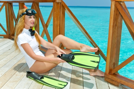 Young pretty woman with flippers, mask and tube at ocean. Maldives. photo