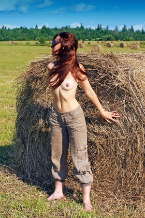 The nude woman in the field near to a haycock. photo